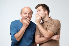 Young caucasian son telling secret to his senior father. Senior man in shock opening his mouth. Young caucasian son telling secret to his senior father. Senior royalty free stock photography