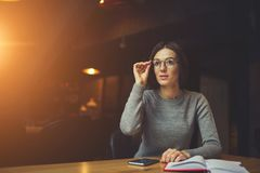 Young caucasian students learning. Intelligent young female freelancer in style eyeglasses sitting in coffee shop at wooden table with notebook and modern Stock Photography