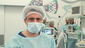 Surgeon poses at the surgery room. Young caucasian surgeon posing at the surgery room. Close up of male medical worker standing against background of his Royalty Free Stock Photo