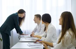 Young caucasian teacher chek and control college students knowledge and skills in classroom stock image