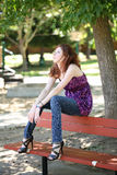 Young caucasian teen girl sitting on park bench Royalty Free Stock Photo