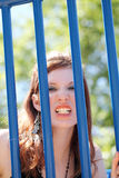 Young caucasian teen girl snarling through bars Stock Photography