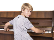 Young caucasian teen plays the piano. Young blond caucasian teen boy plays the piano Royalty Free Stock Images