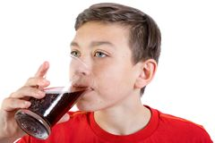 Young caucasian teenage boy drinking cola. Young caucasian teenage boy drinking a glass of cola drink royalty free stock image