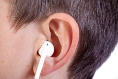 Young caucasian teenage boy`s ear and headphone. Young caucasian teenage boy`s left ear with an ear bud headphone Royalty Free Stock Images
