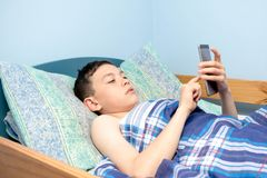 Boy in bed. Young caucasian teenage boy waking up in bed using his phone royalty free stock image