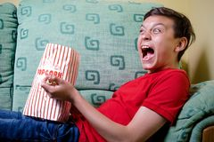 Young caucasian teenage boy watching a scary movie Royalty Free Stock Photos