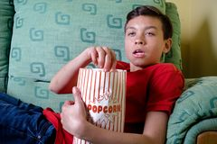 Young caucasian teenage boy watching a scary movie stock photography