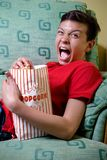 Young caucasian teenage boy watching a scary movie Stock Photo