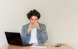Young, Caucasian, thirsty businessman sitting at his desk in front of empty clear wall royalty free stock photography
