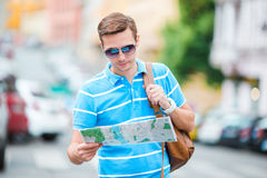 Young caucasian tourist with a city map and backpack in Europe. Happy guy looking at the map of European city in search. Happy young man with a city map and a Stock Photo