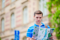 Young caucasian tourist with a city map in Europe outdoors. Happy guy looking at the map of European city in search of. Happy young man with a city map and a Stock Photography