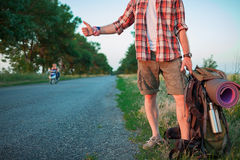 Young caucasian tourist hitchhiking along a road. Young caucasian tourist with backpack hitchhiking along a road in sunset Stock Photography