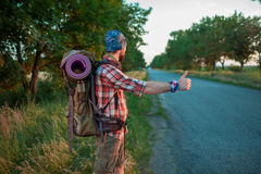 Young caucasian tourist hitchhiking along a road. Young caucasian tourist with backpack hitchhiking along a road in sunset Royalty Free Stock Images