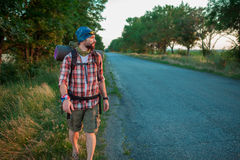 Young caucasian tourist hitchhiking along a road Stock Photo