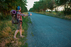 Young caucasian tourist hitchhiking along a road Royalty Free Stock Photos