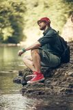 Tourist guy with backpack sitting near lake in a wild summer wood. Expedition. Young caucasian traveler in hiking outfit and red sneakers using digital tablet stock image