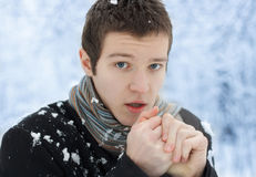 The young caucasian warms hands the breath. on the street in the winter. Royalty Free Stock Images