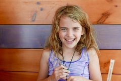 Young girl luaghing and smiling at the camera in a wooden restaurant booth stock images