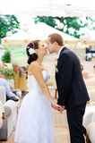 Young caucasian wedding  couple kissing. Young caucasian wedding couple kissing in summer cafe Stock Image