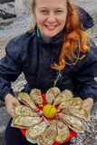 Young Caucasian white woman with red hair holds in her hands a plate with oysters and lemon stock images
