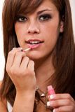 Young caucasian woman applying lipstick Stock Image