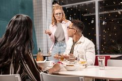 Free Young Caucasian Woman Arguing With Her Boyfriend While He Sitting With Another Girl. Royalty Free Stock Photos - 140676538