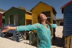 Young Caucasian woman with arms stretched out standing on the beach. Side view of happy gorgeous young Caucasian woman with arms stretched out standing on the royalty free stock image