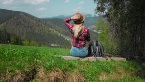 A young caucasian woman with a backpack is sitting on a log on top of a mountain and putting on a hat. The concept of stock video footage