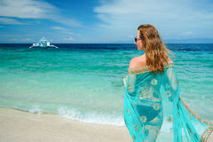 Young caucasian woman with blue sari is staying on the white beach of tropical turcuoise sea at sanny day and getting. Plesaure under blue sky stock images