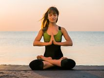 Young caucasian woman in bodysuit relaxing by practicing yoga on the beach near calm sea, close-up of hands, gyan mudra royalty free stock photo