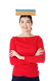 Young caucasian woman with book on her head. Young caucasian woman (student) with book on her head Royalty Free Stock Images