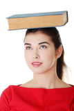 Young caucasian woman with book on her head Stock Photos