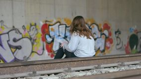 Young Caucasian woman with brown hair sitting on the train tracks. Graffiti on tunnel walls. Slow motion. Concept of despair, depression, danger, exploration stock footage