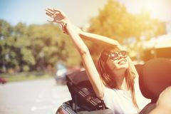 Young woman in cabriolet car departs for the summer holidays royalty free stock images