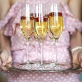 Young woman with champagne glasses on tray. Young caucasian woman with champagne glasses on tray stock photography
