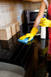 Young caucasian woman cleaning the oven Royalty Free Stock Image