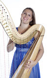 Young caucasian woman with concert harp in studio against white Royalty Free Stock Photos