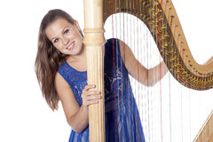 Young caucasian woman with concert harp in studio against white Stock Photo