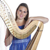 Young caucasian woman with concert harp in studio against white Royalty Free Stock Images