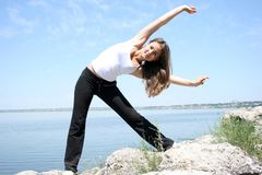Young caucasian woman doing fitness exercises. Against blue sky Royalty Free Stock Image