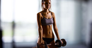 Young Caucasian woman dramatically lifts weights Royalty Free Stock Photography