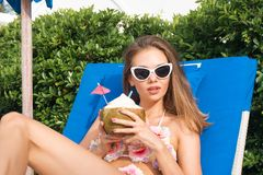 Young Caucasian Woman Drinking Coconut on Sunbed. Young Caucasian Woman with Sunglasses Drinking Coconut on Sunbed Stock Photography