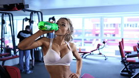 Young caucasian woman drinking at a gym. Young caucasian woman drinking a protein shake at a gym stock footage