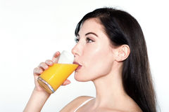 Young caucasian woman drinking orange juice Royalty Free Stock Image