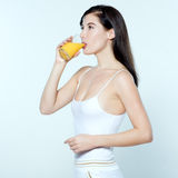 Young caucasian woman drinking orange juice Royalty Free Stock Images