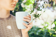 Young Caucasian woman drinks morning coffee from big blue cup being outdoor in spring blossoming garden. Royalty Free Stock Photo