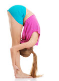 Young caucasian woman is exercising, bending down. Royalty Free Stock Photography