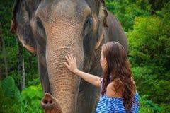 Young Caucasian Woman Feeding an Elephant