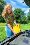 Young caucasian woman fills car motor with oil Royalty Free Stock Photos